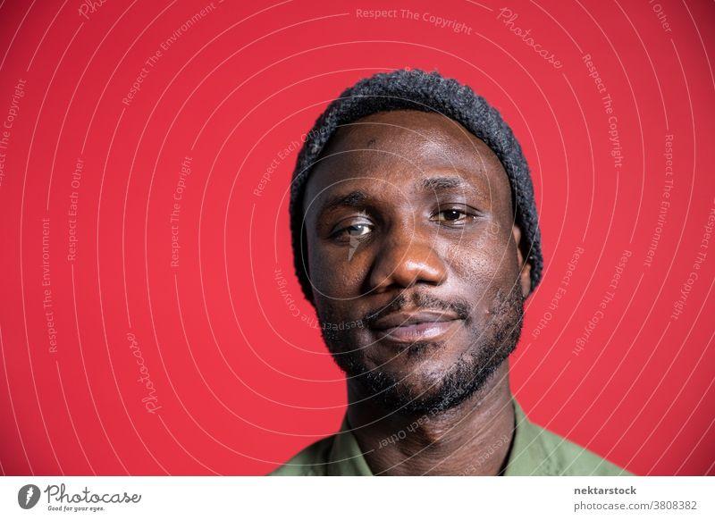 Gesichtsporträt eines jungen schwarzen Mannes vor isoliertem Hintergrund Lächeln afrikanische ethnische Zugehörigkeit Porträt Damenbart männlich