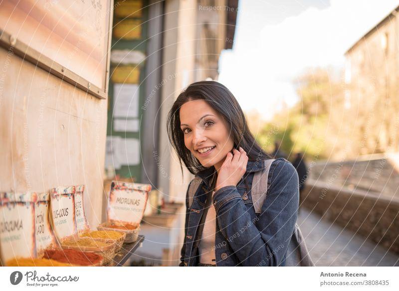 """Hübsche, duftende Frau, Gewürze; spanischer Text: """"Kurkuma, Cous Cous Cous, Gewürz, Paprika"""" Sie macht Tourismus in Granada, Spanien und besucht Orte in der Nähe von """"La Alhambra""""."""