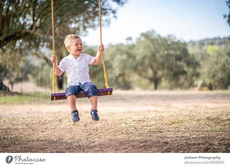 Süßes blondes Kleinkind auf der Schaukel pendeln Junge niedlich Glück genießen Vergnügen Vorschulkind Kinder Sitzen Sommerzeit Freizeit Freiheit Lachen männlich