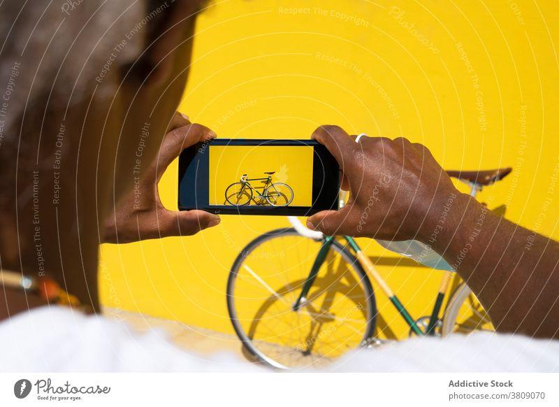 Schwarzer Mann nimmt ein Foto von seinem Fahrrad mit dem Telefon auf einem gelben fotografierend Mobile Online-Verkauf ein Fahrrad verkaufen