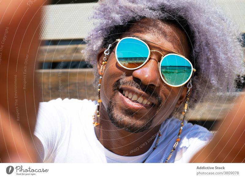 Schwarzer Mann mit Afro-Haar lächelnd und nehmen ein Selfie. Schwarzer Mann einen Selfie nehmend Afrohaar schwarz Lächeln Afrikanisch Amerikaner Afro-Look