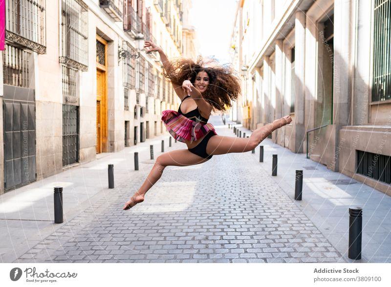 Fröhliche junge ethnische Ballerina springt auf der Straße Frau springen Glück Tanzen ausführen Balletttänzer Lächeln beweglich Energie Bewegung Tänzer passen