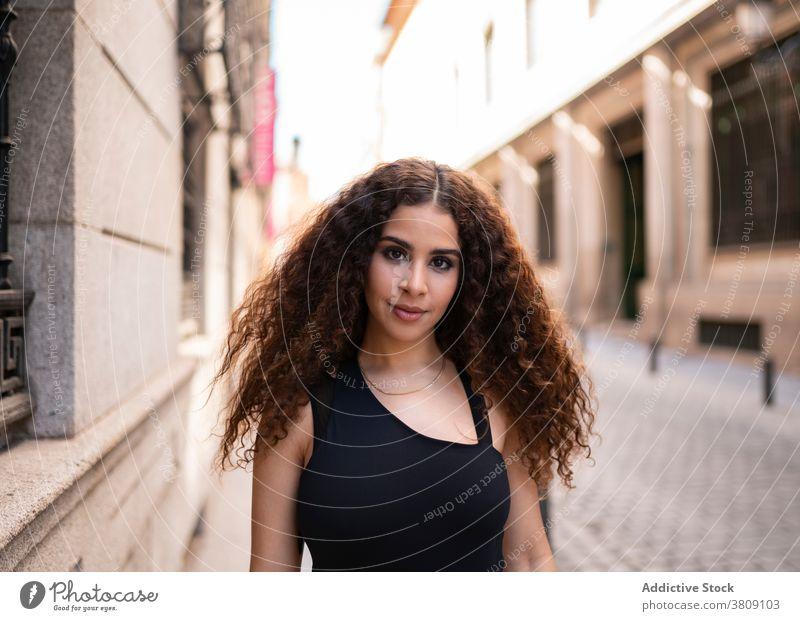 Verführerische junge ethnische Frau entspannt auf der Straße selbstsicher Stil Lächeln Großstadt Verlockung Anmut Vorschein Porträt Glück ruhen Außenseite