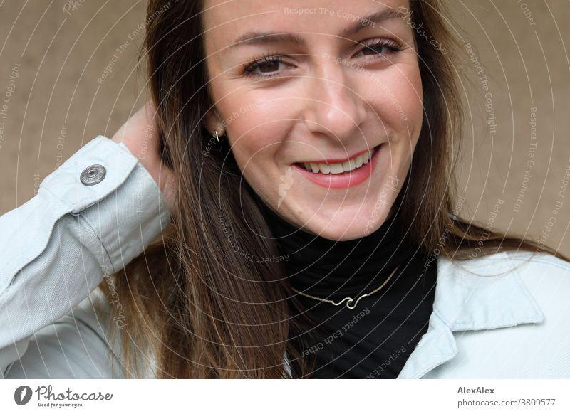 Nahes Portrait einer jungen, lächelnden Frau mit Grübchen in Jeansjacke 18-30 Jahre schön fit schlank schlau freundlich angenehm attraktiv brünett langhaarig