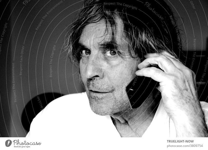 Störe mich nicht beim Telefonieren scheint der etwas wild aussehende und dreinschauende, unrasierte Mann mit langen Haaren im Halbprofil mit weißem T-Shirt zu denken, während er ein schnurloses Telefon an sein Ohr hält
