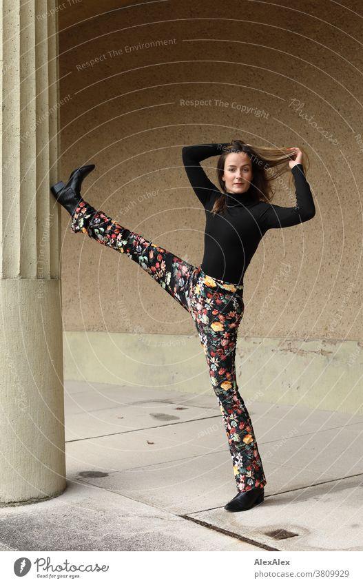 Portrait einer jungen Tänzerin die ein Bein an einer Säule hoch hält Frau 18-30 Jahre schön fit schlank schlau freundlich angenehm attraktiv brünett langhaarig