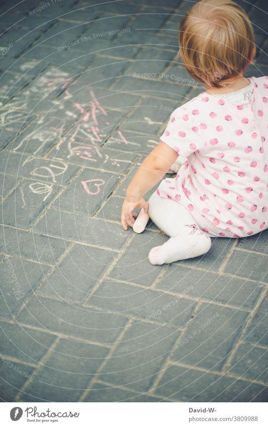 Kind malt mit Kreide auf dem Boden malen kreativität Mädchen Straßenmalkreide beschäftigung Kindheit Spaß