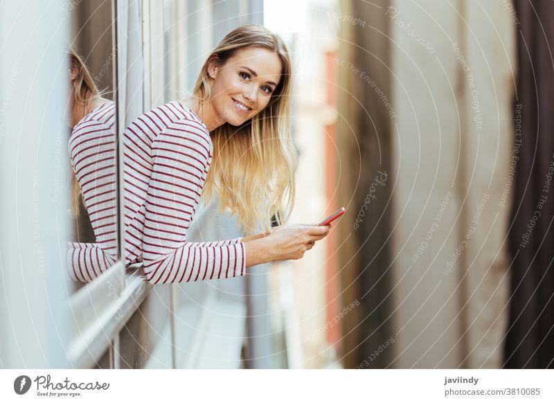 Junge Frau lehnt sich mit einem Smartphone aus dem Fenster ihres Hauses. Erwachsener attraktiv Hintergrund schön Schönheit schwarz Anruf lässig Kaukasier Zelle