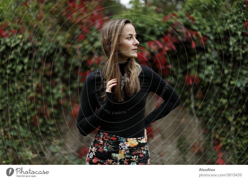 Seitliches Portrait einer jungen Frau vor einer Mauer mit Efeu und wildem Wein 18-30 Jahre schön fit schlank schlau freundlich angenehm attraktiv brünett
