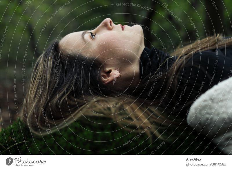 Seitliches Portrait einer jungen Frau die auf einem Mooshügel im Wald liegt und nach oben schaut 18-30 Jahre schön fit schlank schlau angenehm attraktiv brünett