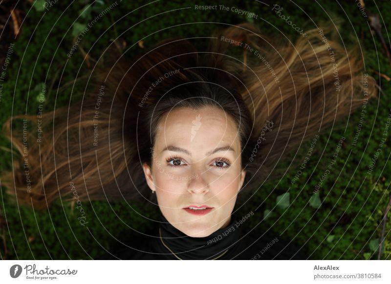 Portrait einer jungen Frau die auf einem Mooshügel im Wald liegt und nach oben schaut 18-30 Jahre schön fit schlank schlau angenehm attraktiv brünett langhaarig