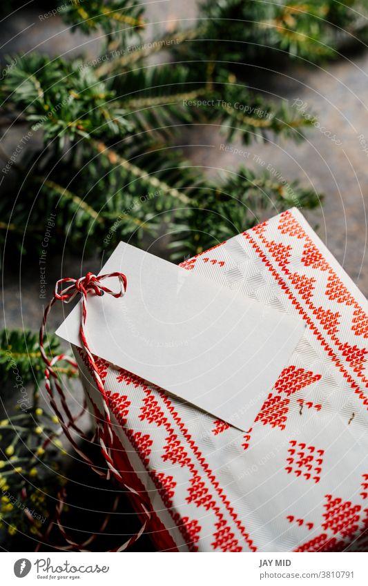 Verpackte Weihnachtsgeschenkschachtel, mit leerem Etikett und rotem Klebeband, umgeben von Kiefernzweigen auf grunge-blauem Hintergrund Kasten Geschenk Tag