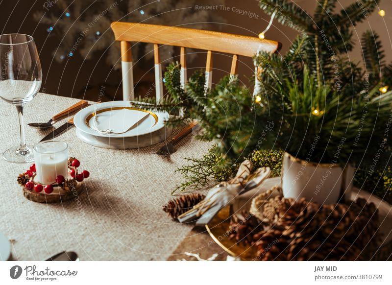 Gemütlich gedeckter Weihnachtstisch, dekoriert mit Kiefernzweigen und rustikaler Tischdecke im Wohnzimmer mit Baumbeleuchtung Weihnachten Erntedankfest Gedeck