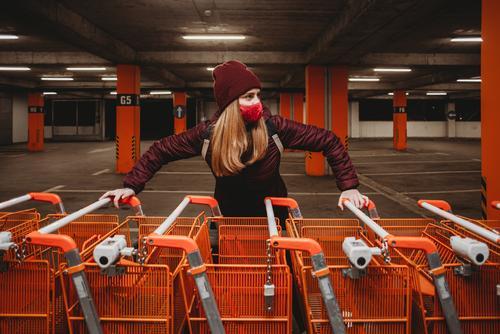 Frau mit Maske, die eine Reihe orangefarbener Einkaufswagen in der Garage hält attraktiv Tasche schön große Einkaufswagen Parkplatz Kaukasier Großstadt Kleidung