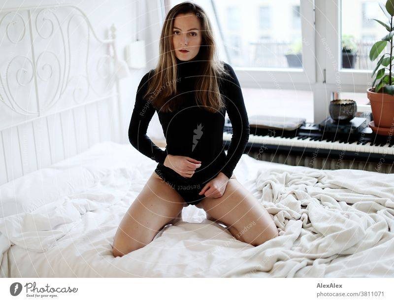 Nahes Portrait einer jungen Frau die auf einem Bett kniet und in die Kamera schaut 18-30 Jahre schön fit schlank schlau freundlich angenehm attraktiv brünett