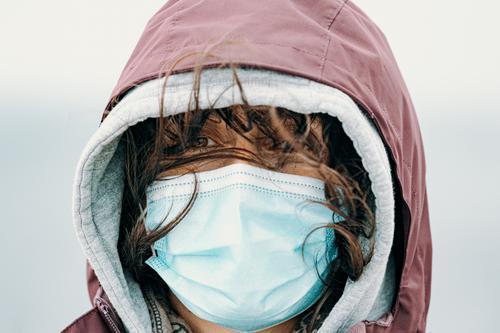 Nahaufnahme des Gesichts einer Frau mit aufgesetzter Maske und durch den Wind fliegenden Haaren in Wanderkleidung und mit direktem Blick in die Kamera Roman