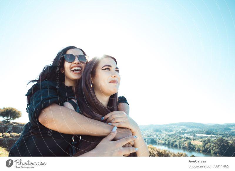 Zwei Frauen, die sich an einem sonnigen Tag amüsieren, während sie lächeln und sich mit Kopierraum umarmen Freundschaft Freude Sonne Fröhlichkeit jung