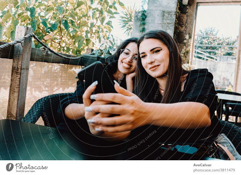 Ein Paar junge Frauen, die lächelnd in einer Bar ein Selfie machen Foto Telefon Glück brünett Freunde freudig Dame tausendjährig außerhalb Lächeln stylisch