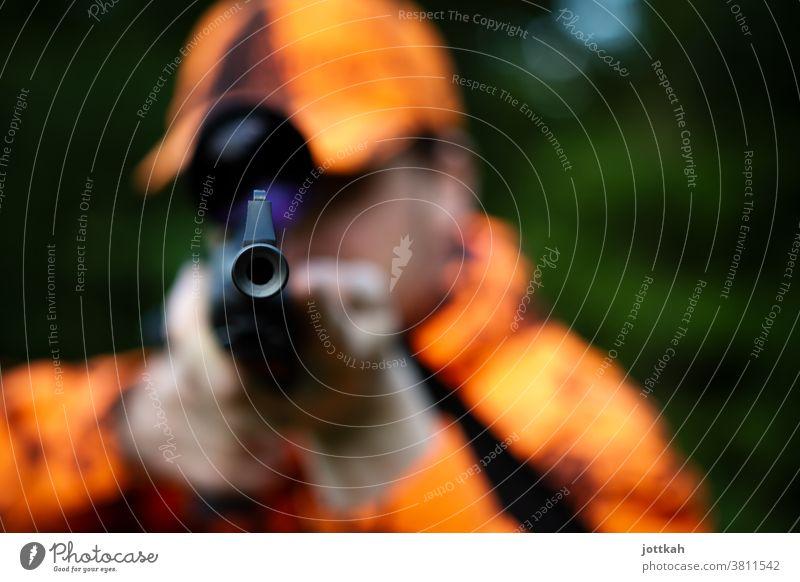 Blick in den Lauf eines Jagdgewehrs, das von einem orange gekleideten Jäger gehalten wird. Der Fokus liegt auf der Mündung der Waffe. Gewehr Flinte Schusswaffe