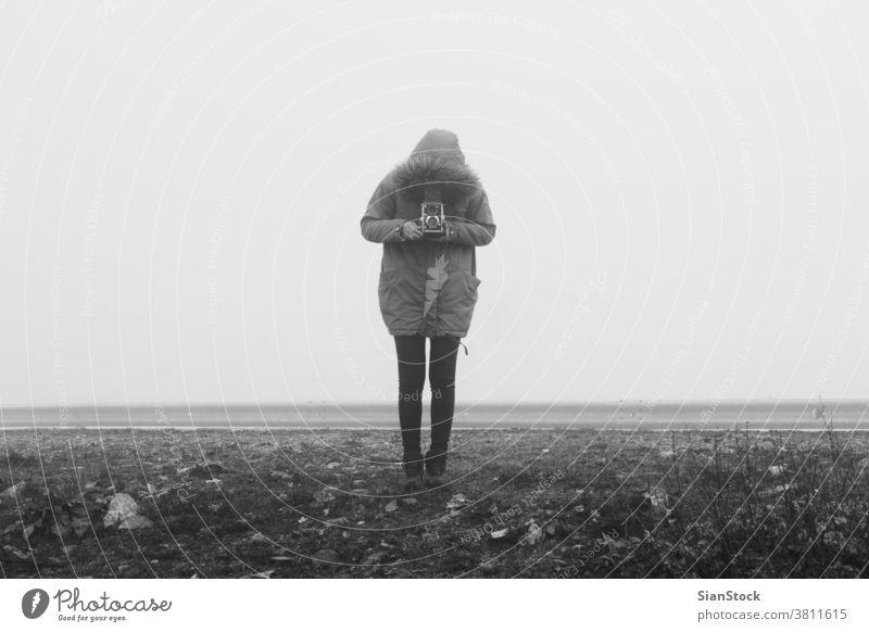 Frau mit Retro-Kamera in einer Nebel-Landschaft Fotokamera neblig schwarz weiß SCHWARZ-WEIß altehrwürdig Winter Kunst retro Mädchen unter Person Fotograf