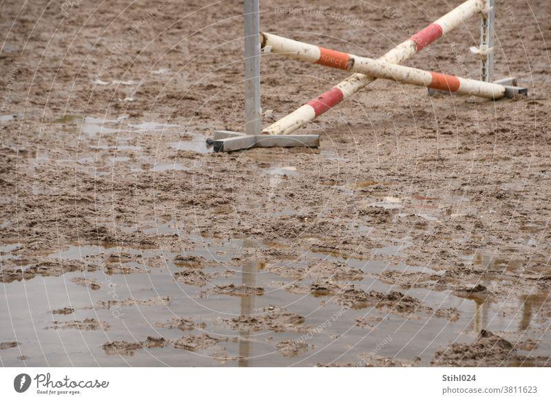 Pferdesportplatz mit gekreuztem Hindernis versinkt im Matsch mit Pfütze Springreiten Hindernisreiten Schlamm überflutet Ständer rot-weiß BArriere Hürde Palisade