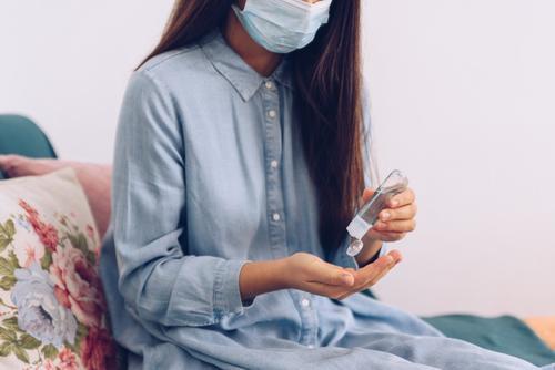 Coronavirus-Konzept. Ein Mädchen in ihrer Wohnung hat sich zum Schutz vor dem Coronavirus ein antiseptisches Gel auf die Hände aufgetragen. Weltweiter Aufruf, zu Hause zu bleiben.