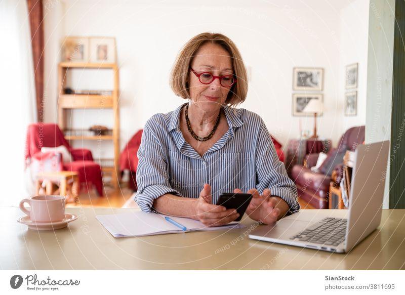 Senioren mittleren Alters, die zu Hause am Computer arbeiten Frau Laptop reif Menschen eine Telefon Smartphone Nachricht Talkrunde Person Lifestyle Schreibtisch