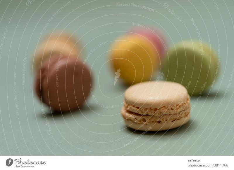 Bunte, schmackhafte Makronen über einem grünen Hintergrund. In einer Reihe orange purpur Studioaufnahme appetitlich angeordnet Backwaren backen