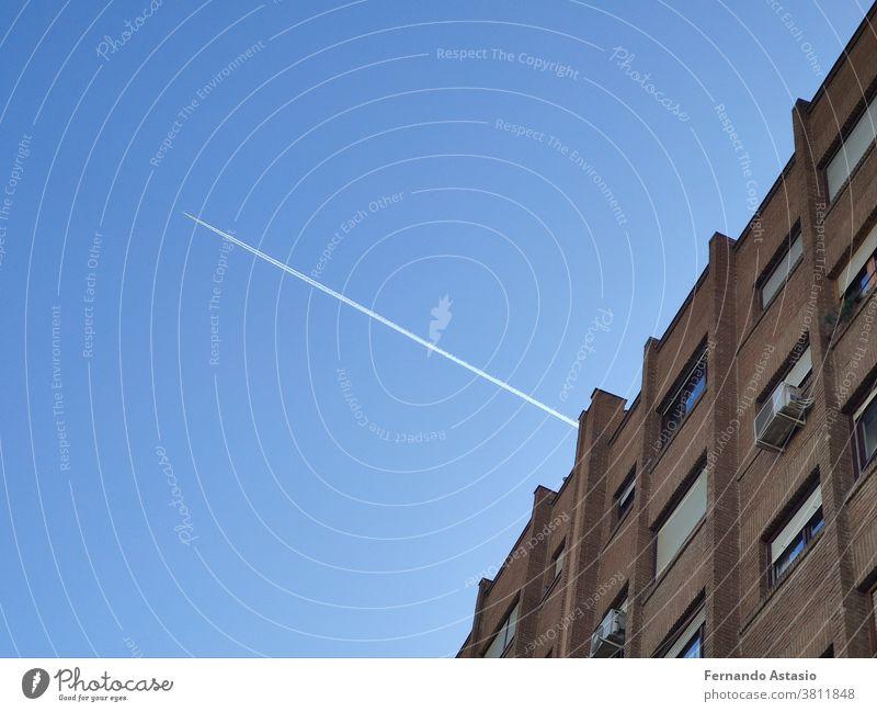 Der weiße Blitz des Flugzeugs, das durch das Gebäude geflogen ist und die Linien zerschnitten hat, in Madrid, Spanien Architektur Himmel Wolkenkratzer Großstadt