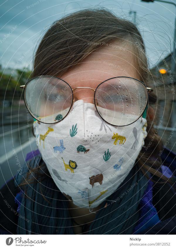 junge Frau trägt eine Maske und eine beschlagene Brille im Herbst / Winter (Corona / Covid-19) Junge Frau Maskenpflicht Hygienevorschrift COVID-19 Beschlagen