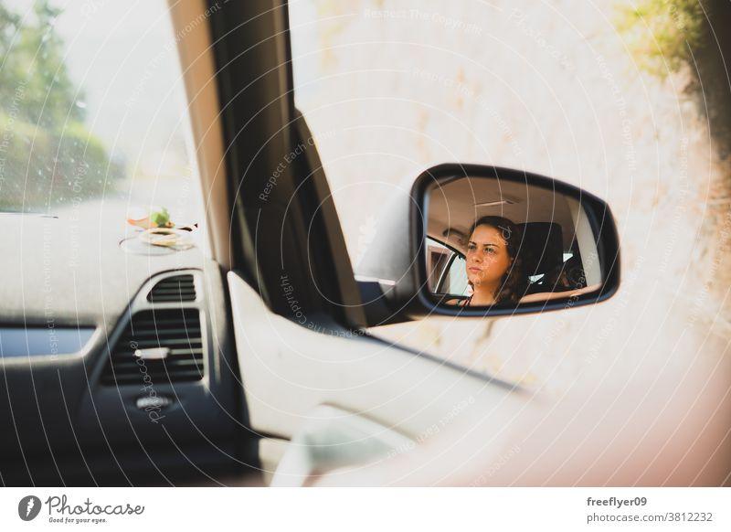 Blick einer jungen Frau auf den Rückspiegel eines Autos fahren Rückansicht PKW Verkehr Ausflug Autoreise Straße Porträt Fahrer Spiegel Gesicht schön reisen
