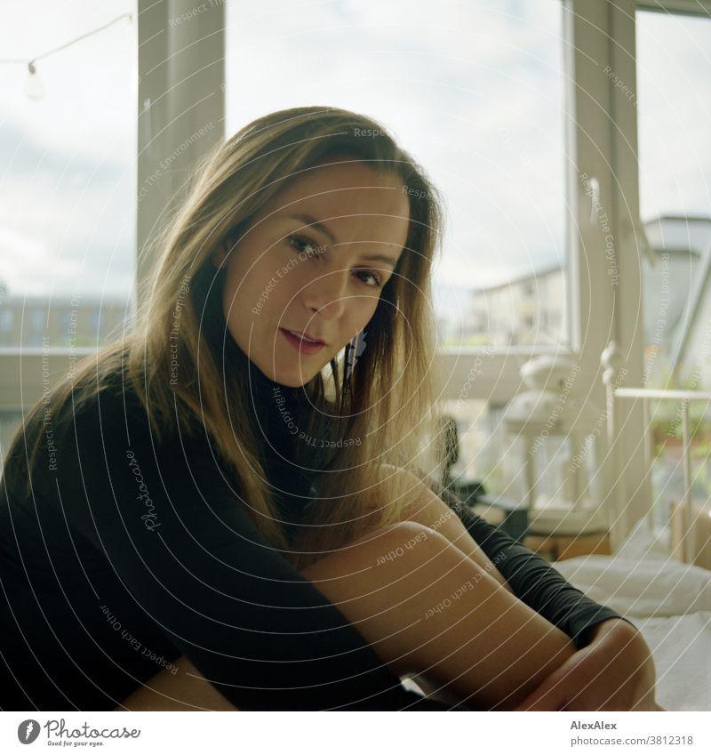 Analoges, nahes Portrait einer jungen Frau die auf einem Bett sitzt und in die Kamera schaut 18-30 Jahre schön fit schlank schlau freundlich angenehm attraktiv