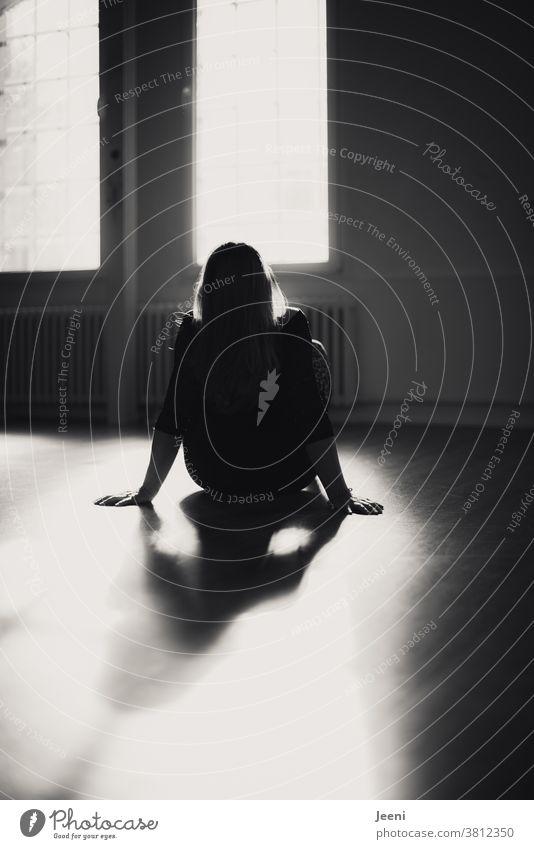 Frau im Gegenlicht entspannt sich nach dem Tanzen im Tanzstudio Junge Frau Atelier Erholung feminin Sonne Silhouette Licht Sonnenlicht Tänzerin Umrisslinie