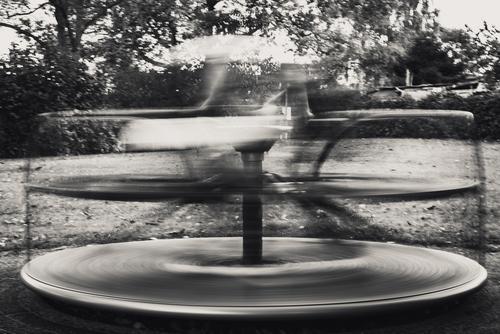 Kinder auf dem Spielplatz drehen sich schnell im Karussel bis ihnen schwindelig wird Karussell Drehung Kreis im Kreis Kreisel Freude spielen Bewegung