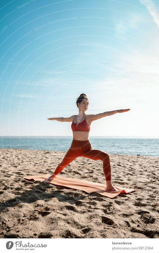 Junge erwachsene Frau praktiziert Yoga am Strand, Virabhadrasana II-Pose Übung Training MEER Gesundheit sportlich Aktivität Erholung Fitness Lifestyle friedlich