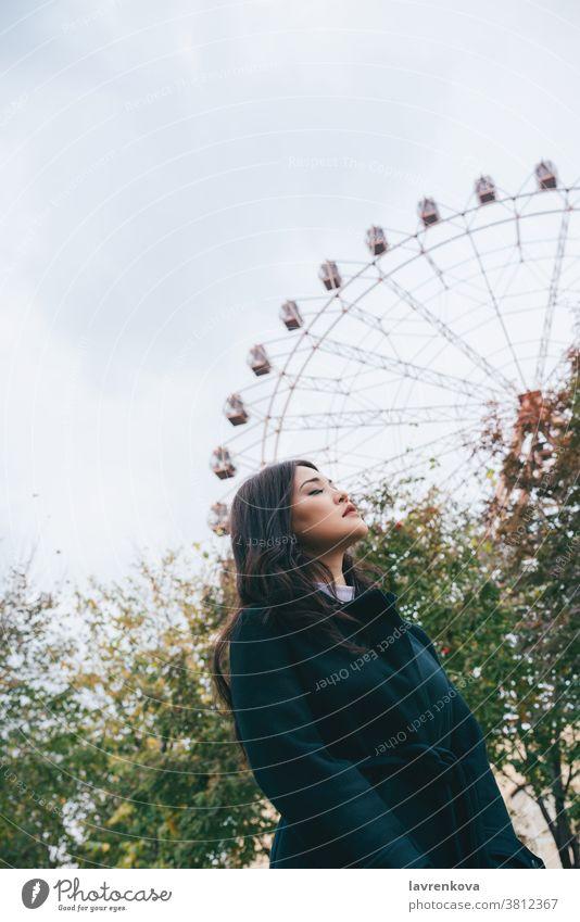 Junge erwachsene Asiatin in dunklem Mantel vor dem Riesenrad im Freien, selektiver Fokus Frau asiatisch Herbst Park lässig Freizeit saisonbedingt Wochenende