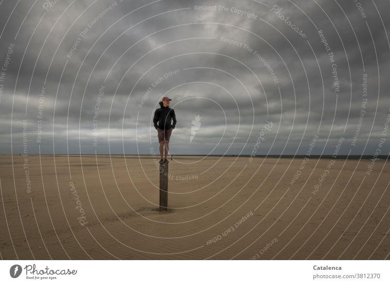 Aussichtsreich, Mann  steht auf einem Pfosten am Strand an einem bewölktem Tag Meer Küste Nordsee Himmel Horizont Personen Sandstrand Hozizont Wolken