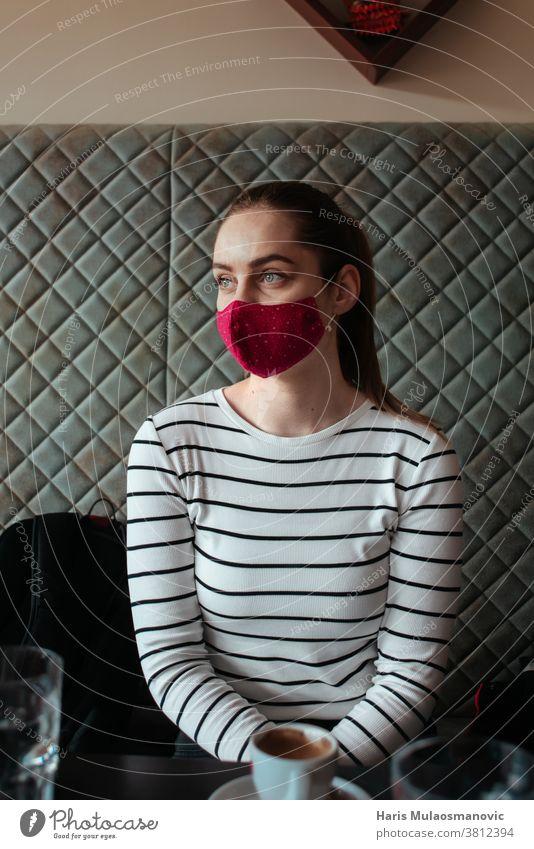 Frau mit Gesichtsmaske, Reisende beim Aufwärmen im Café Rucksack Taschen Café-Laden Kaukasier Kaffeehaus cool Corona-Virus COVID covid-19 Tasse gefeuert Zukunft