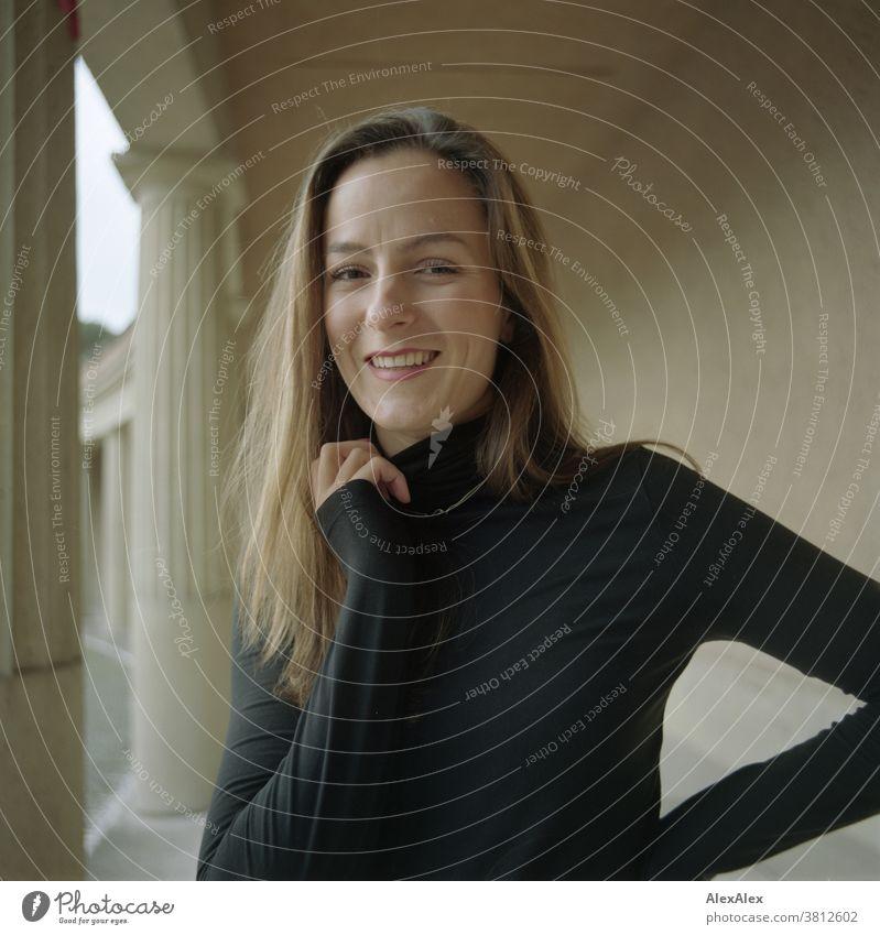 Nahes Portrait einer lächelnden, jungen Frau mit Grübchen in einem Säulengang 18-30 Jahre schön fit schlank schlau freundlich angenehm attraktiv brünett