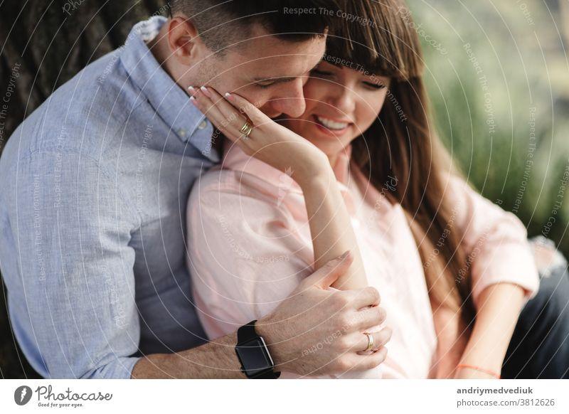 Bild Nahaufnahme eines glücklichen, fröhlichen Paares in Sommerkleidung, das beim Spaziergang im Park lächelt und sich umarmt. Sie küssen und umarmen sich. selektiver Fokus