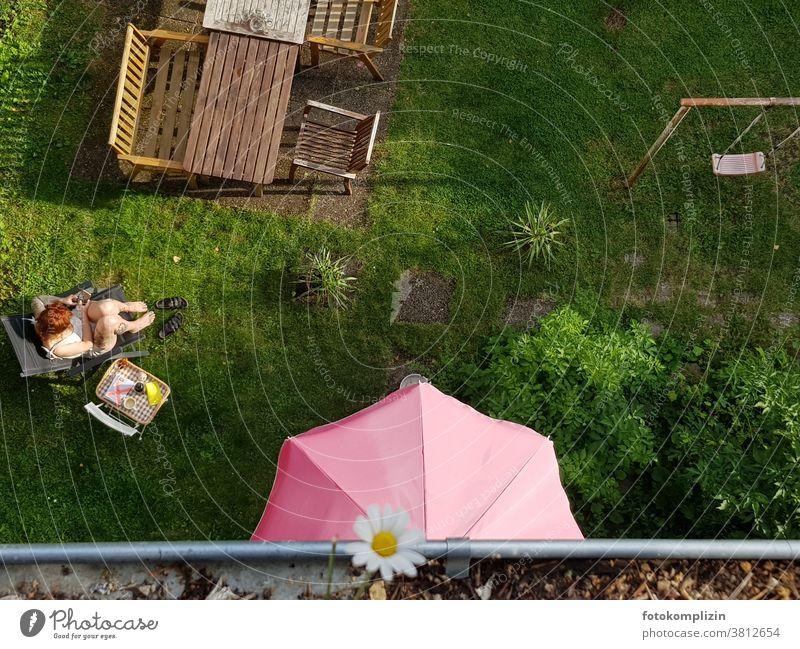 Blick von oben in einen Garten mit Tisch, Tablett, Stühle, Schaukel, Sonnenschirm und Frau Gartenmöbel Gartentisch junge Frau Pause chillen Pause machen Stuhl