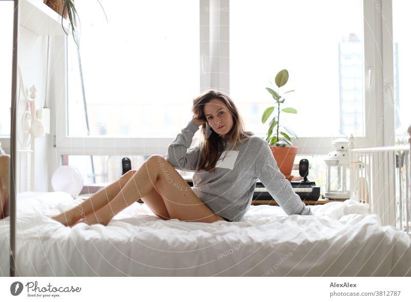 Nahes Portrait einer jungen Frau die auf einem Bett sitzt 18-30 Jahre schön fit schlank schlau freundlich angenehm attraktiv brünett langhaarig gesund frisch
