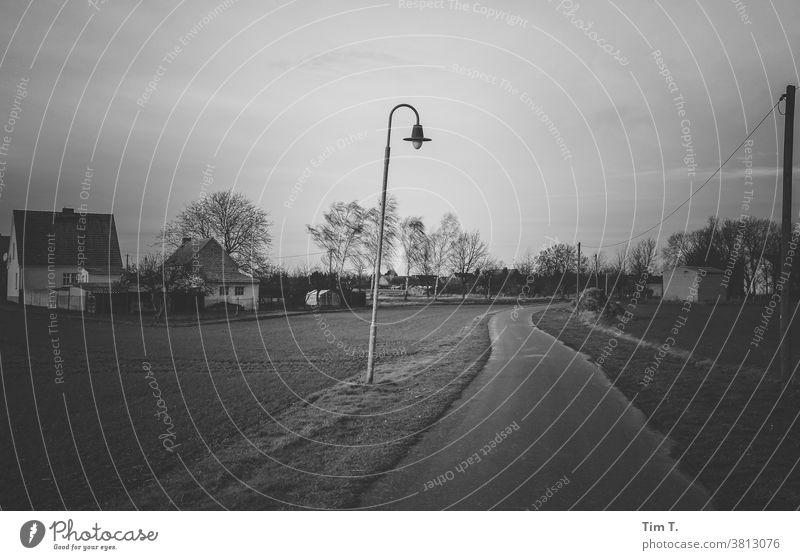 Stille Tage in der Uckermark Dorf s/w b/w Schwarzweißfoto ruhig b&w Einsamkeit Architektur Laterne Straße dunkel Winter Herbst Abenddämmerung Ort Brandenburg