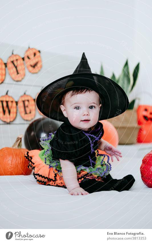 hübsches kleines Mädchen in Hexen-Halloween-Kostüm zu Hause, auf dem Bett sitzend mit Halloween-Dekoration, Lifestyle drinnen Tracht heimwärts im Innenbereich