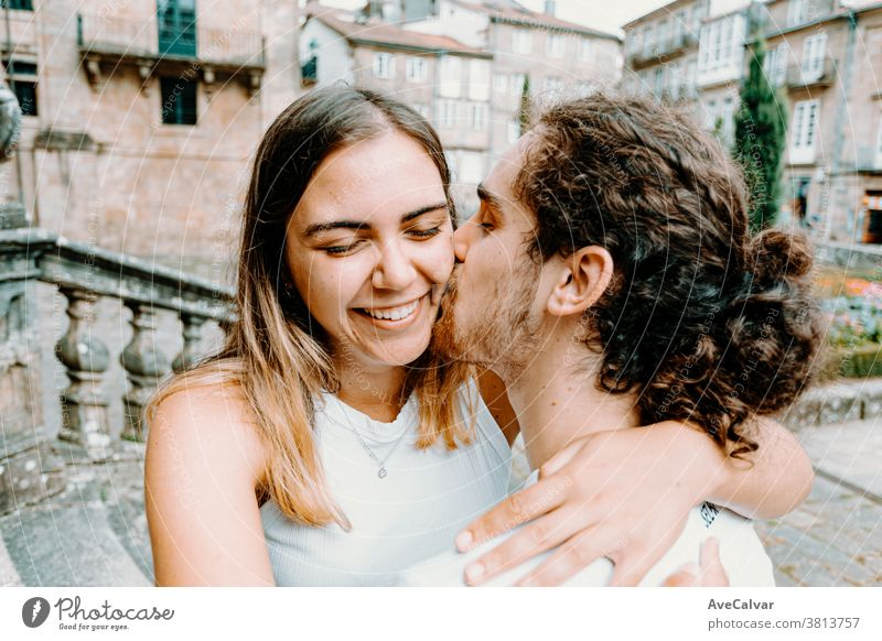 Junger Mann küsst seine Freundinnen, während sie lächelt Erwachsener Gefühl weiß Spaß Porträt Pose Frau umarmend jung Paar Halt Fröhlichkeit grinsen Kaukasier