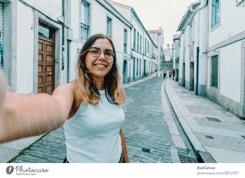Junge Frau mit Brille bei einem Selbstmord auf einer alten spanischen Straße hübsch Smartphone trendy freudig brünett im Freien modern Schönheit Stil