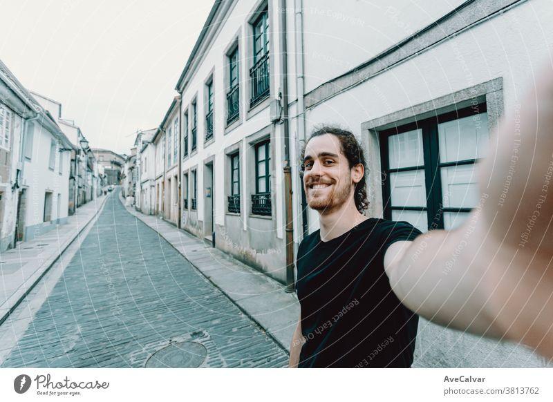 Junger Mann mit Brille bei einem Selbstmord auf einer alten spanischen Straße Foto Urlauber modern bärtig Porträt heiter Glück Hafengebiet Rucksack Selfie
