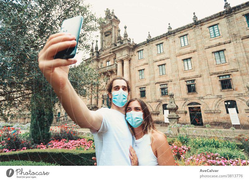 Junges Paar, das sich mit den Masken in einem Garten vor einem alten Gebäude vergnügt männlich Virus Mann Person Mundschutz Familie reisen Frau Ausbruch