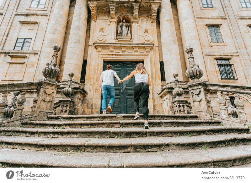 Junges Paar geht an einem sonnigen Tag in einem alten Gebäude eine Treppe hinauf und fasst sich an den Händen außerhalb Urlauber Mann Treppenhaus im Freien
