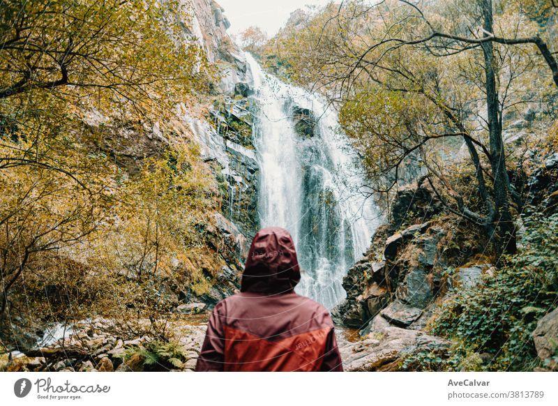 Unscharfe Frau in violettem Ölzeug steht vor einem riesigen Wasserfall Rucksack im Freien Wald Menschen Blick Ansicht weiß Abenteuer sonnig erkundend genießen